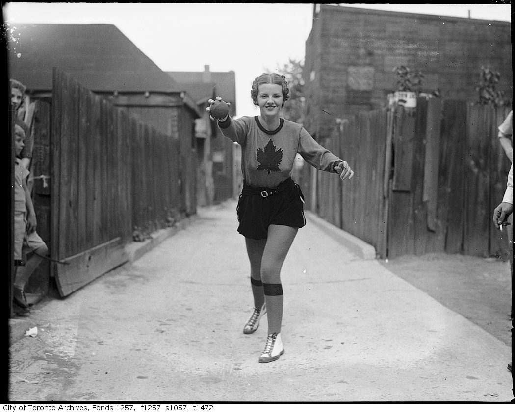 Billie Hallam, Miss Toronto 1937, wearing Toronto Maple Leafs Baseball Club outfit, striking baseball pose in alley 1937