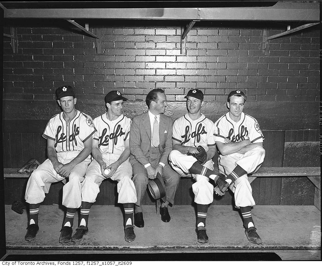 Jack Kent Cooke with baseball players in Toronto Maple Leafs Baseball Club dugout, Maple Leaf Stadium 195?