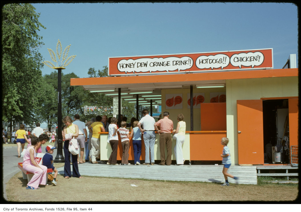 1974 - View of people standing at food stand on CNE grounds