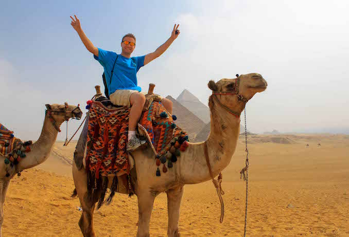 Joey taking a camel ride at the Pyramids of Giza in Egypt