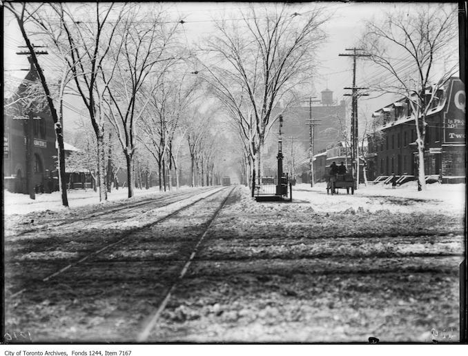 Toronto Winter Photographs Spadina Avenue, looking south from Queen Street. - Febraury, 1914 - photograph. The railings at centre denote the entrance to the underground public lavatory.