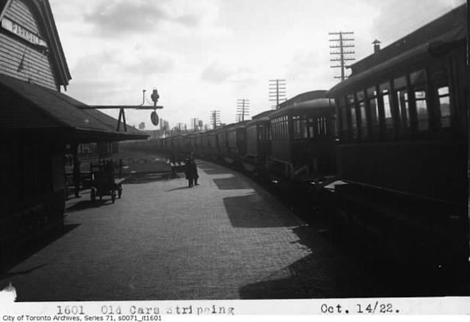 photograph of old Toronto Railway Company streetcar being sent on Canadian National Railway flatcars at Parkdale Station. One of many old car bodies slupped north to Haileybury, Ontario to serve as temporary housing due to recent forest fire that devastated the town taken October 14, 1922.