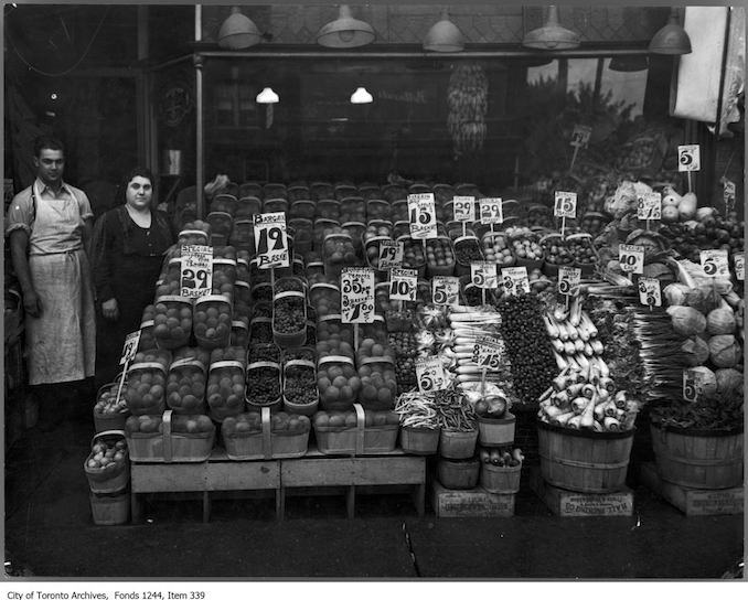 photograph of Tony Greco and his mother at their fruit and vegetable store, Danforth Fruit, on the southwest corner of Danforth and Logan avenues - 1930?