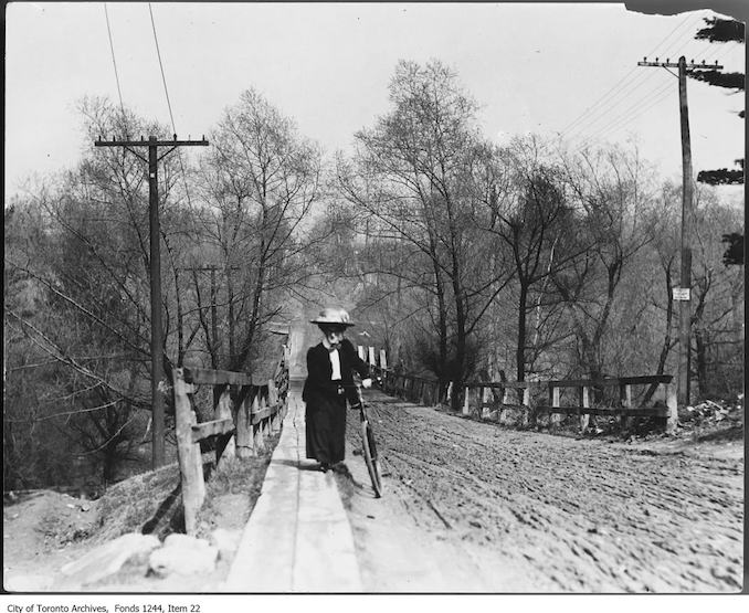 Female cyclist wheeling bicycle up muddy hill on St. Clair Avenue West. - 1907 - Vintage Bicycle Photographs