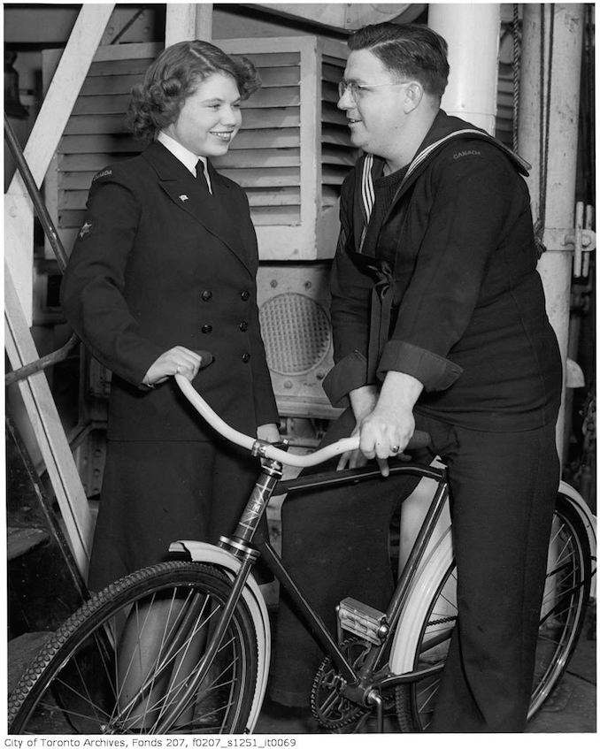 "HMCS ""Forest Hill"" crew host WRENS stationed in Halifax from Forest Hill Village, and other parts of Toronto at a dinner on the ship : Coder James Cramer (1300 Lansdowne Ave.) shows WREN Ruth Arnsby (9 Montclair) one of the bicycles sent by the Village of Forest Hill to the ship 1940-45 - Vintage Bicycle Photographs"