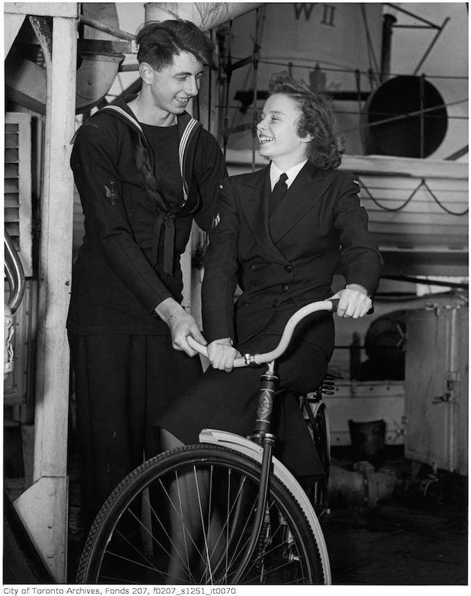 "Mary J. Gilmore and Ordinary Seaman Robert Denyer try out one of the bicycles - HMCS ""Forest Hill"" crew host WRENS stationed in Halifax from Forest Hill Village, and other parts of Toronto at a dinner on the ship : Coder James Cramer (1300 Lansdowne Ave.) shows WREN Ruth Arnsby (9 Montclair) one of the bicycles sent by the Village of Forest Hill to the ship 1940-45 - Vintage Bicycle Photographs"