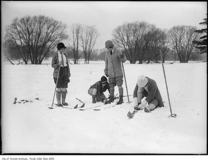 Ski-ing, four girls putting on skis. - January 17, 1926 - vintage skiing photographs