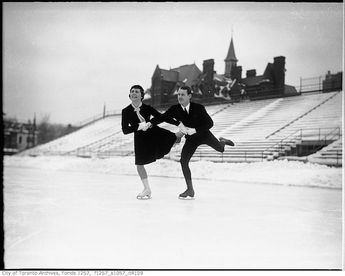 Stewart Reburn and Sonie Henie, skating team, skating on rink in Varsity Stadium