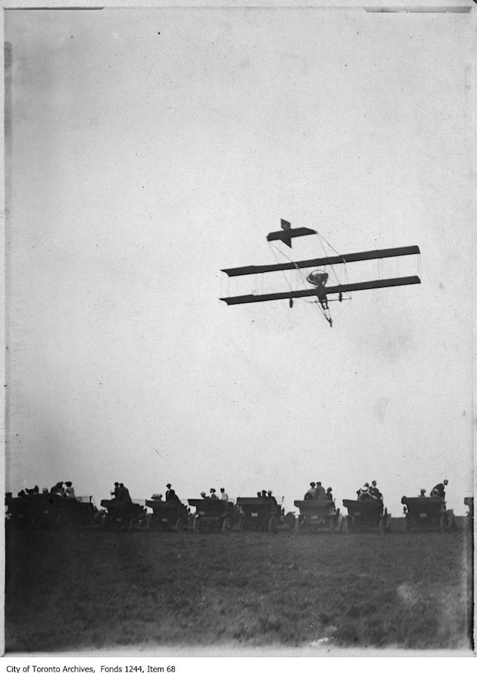 photograph of an airplane in flight. Information provided by a researcher indicates that the airplane is probably a Curtiss-type Pusher bi-plane with inset ailerons and rotary engine, flown by Charles F. Willard, and that the event may be the Aviation Meet held at Donlands Farm, Todmorden Mills, August 3-5, 1911.