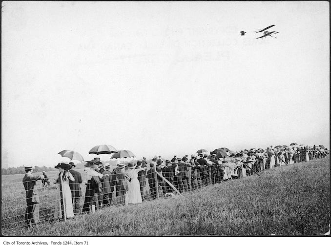 photograph of an airplane in flight over a crowd. Information provided by a researcher indicates that the airplane is probably a Curtiss-type Pusher bi-plane with inset ailerons and rotary engine, flown by Charles F. Willard, and that the event is probably the Aviation Meet held at Donlands Farm, Todmorden Mills, August 3-5, 1911.