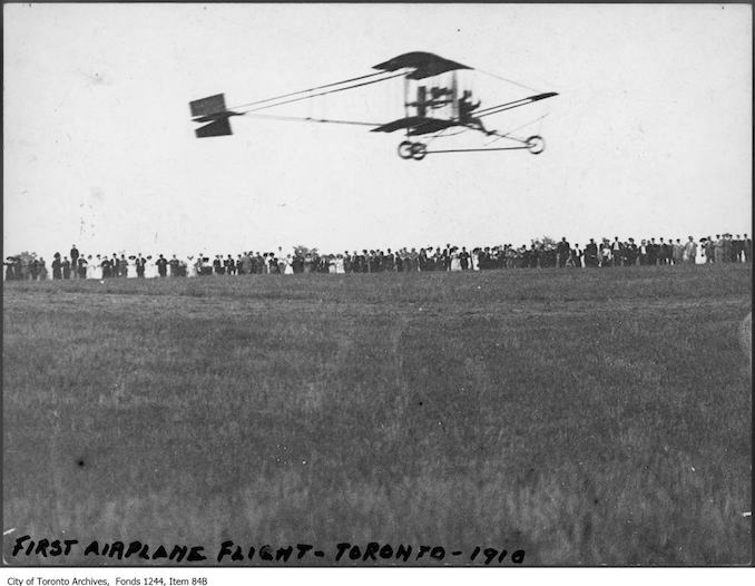 Airplane taking off. - 1910 - photograph of an airplane taking off. Information provided by a researcher indicates that the airplane is probably a Curtiss-type Pusher bi-plane with inset ailerons and rotary engine, flown by Charles F. Willard, and that the event is probably either the Aviation Meet held at Donlands Farm, Todmorden Mills, August 3-5, 1911, or the Aviation Meet, Hamilton, July 27-29, 1911.