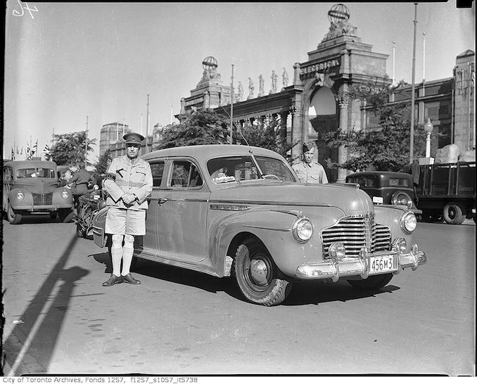 Armed forces men and automobile in OC Cavalcade, by Princes' Gates 1941