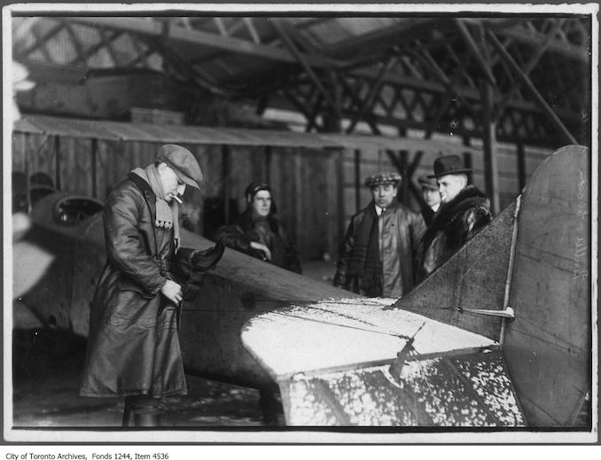 Aviator Bert Acosta prepares to take William James Sr. up in airplane, Leaside. - 1916 - photograph taken just before William James Sr. took the first movies from the air in Canada. Other subjects include F.G. Ericson (in checkered cap) and head of construction Sir Frank Baillie (right) - Vintage Airplane Photographs