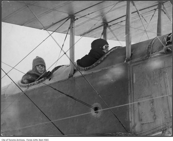 Aviator Bert Acosta prepares to take William James Sr. up in airplane, Leaside. - 1916 - photograph taken just before William James Sr. took the first movies from the air in Canada. Other subjects include F.G. Ericson (in checkered cap) and head of construction Sir Frank Baillie (right). - photograph . Baillie was the head of airplane construction. The pilot is Bert Acosta. The plane is a Jenny JN4.