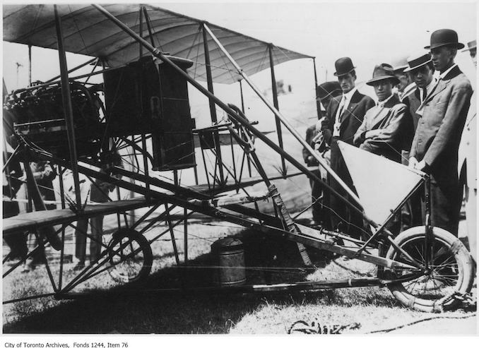 Lincoln Beachey's airplane. - 1910 - photograph of men examining an airplane. Information provided by a researcher indicates that the airplane is probably Lincoln Beachey's Curtiss-type Pusher bi-plane with 8-cylinder Curtiss V-8 engine and no forward control surfaces, and that the event is probably the Buffalo Aero Club Aviation Meet, Fort Erie, Ontario, June 20-24, 1911. The man with his arms folded is Frank H. Ellis, author of Canada's Flying Heritage.