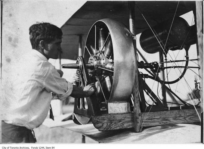 Man working on McCurdy's plane. - 1910 - photograph of a man working on an airplane engine. Information provided by a researcher indicates that it is probably J.A.D. McCurdy's bi-plane with 7-cylinder Gnome rotary engine, and that the event is probably either the Aviation Meet held at Donlands Farm, Todmorden Mills, August 3-5, 1911, or the Aviation Meet, Hamilton, July 27-29, 1911.