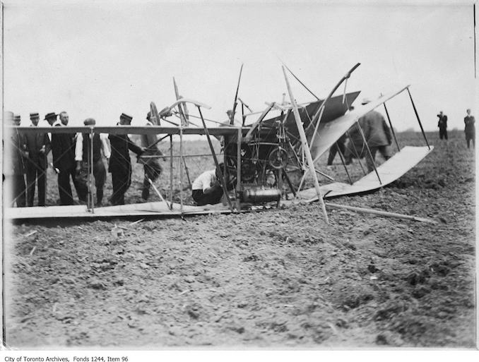 Men inspecting wreckage of first Toronto airplane crash. - 1911 - photograph of an airplane crashed on the ground. Information provided by a researcher indicates that it is probably a bi-plane with 7-cylinder Gnome rotary engine, flown by J.A.D. McCurdy, and that the event is probably the Aviation Meet, Donlands Farm, Todmorden Mills, August 3-5, 1911.