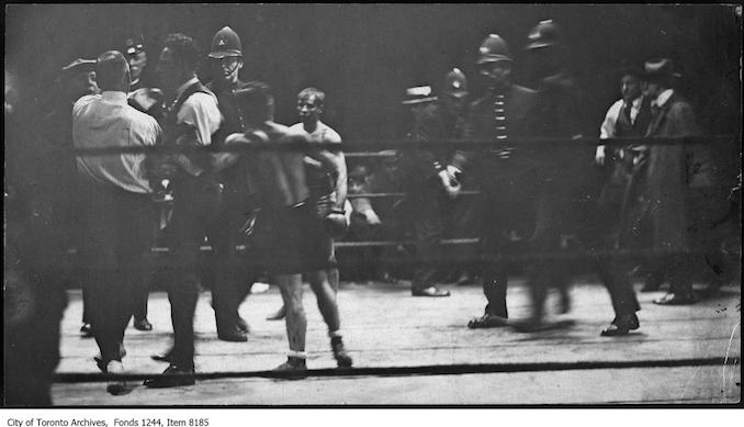 Police go into the ring to protect referee Lou Marsh (left) at Patsy Wallace vs. Jimmy Wilde boxing match at CNE. - May 24, 1920