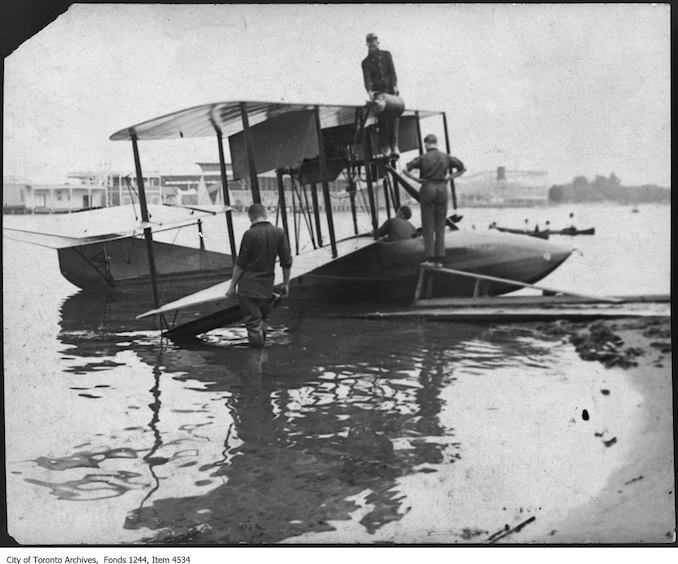 Putting gasoline in T.C. MacCauley's Curtiss F flyboat. - 1915 - photograph. The airplane may have been called the Maple Leaf.