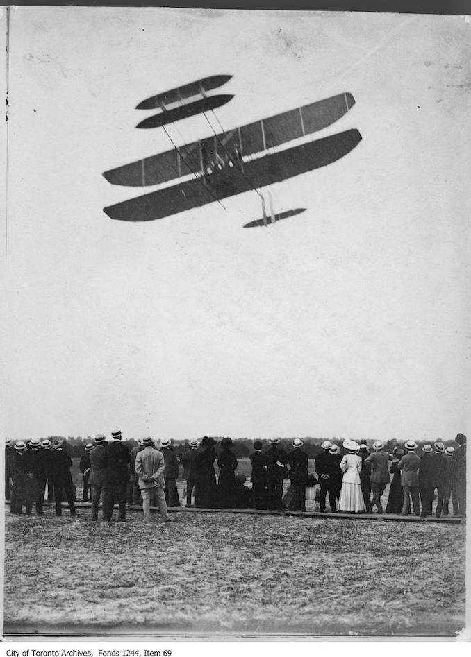 Ralph Johnstone flying box kite airplane. - July, 1910 - photograph of an airplane in flight. Information provided by a researcher indicates that the airplane is probably a 1909 Model A (Transitional) bi-plane flown by Ralph Johnstone of the Wright Exhibition Company, and that the event is probably the Ontario Motor League Aviation Meet held at Trethewey Model Farm, Weston, July 8-16, 1910.