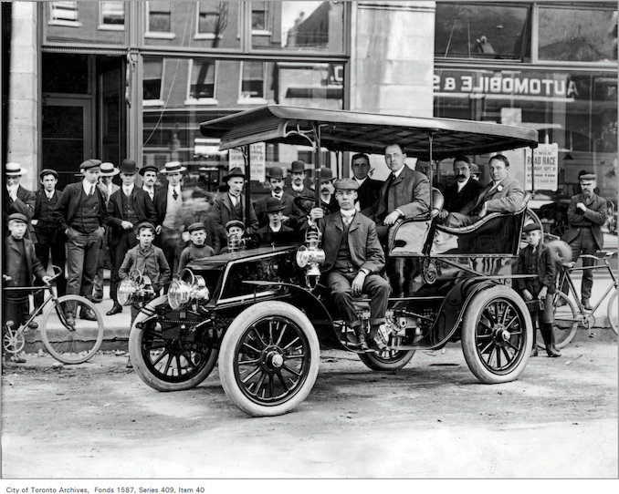 men in auto with group of on-lookers, on Temperance St., across from the Automobile and Supply Co. Ltd., 22-26 Temperance St 1902