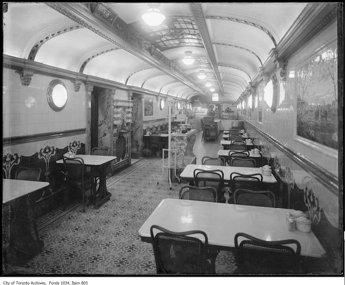 ca. 1916 - Interior of long narrow restaurant with bentwood chairs, mosaic floor and ceiling reminiscent of a railway car