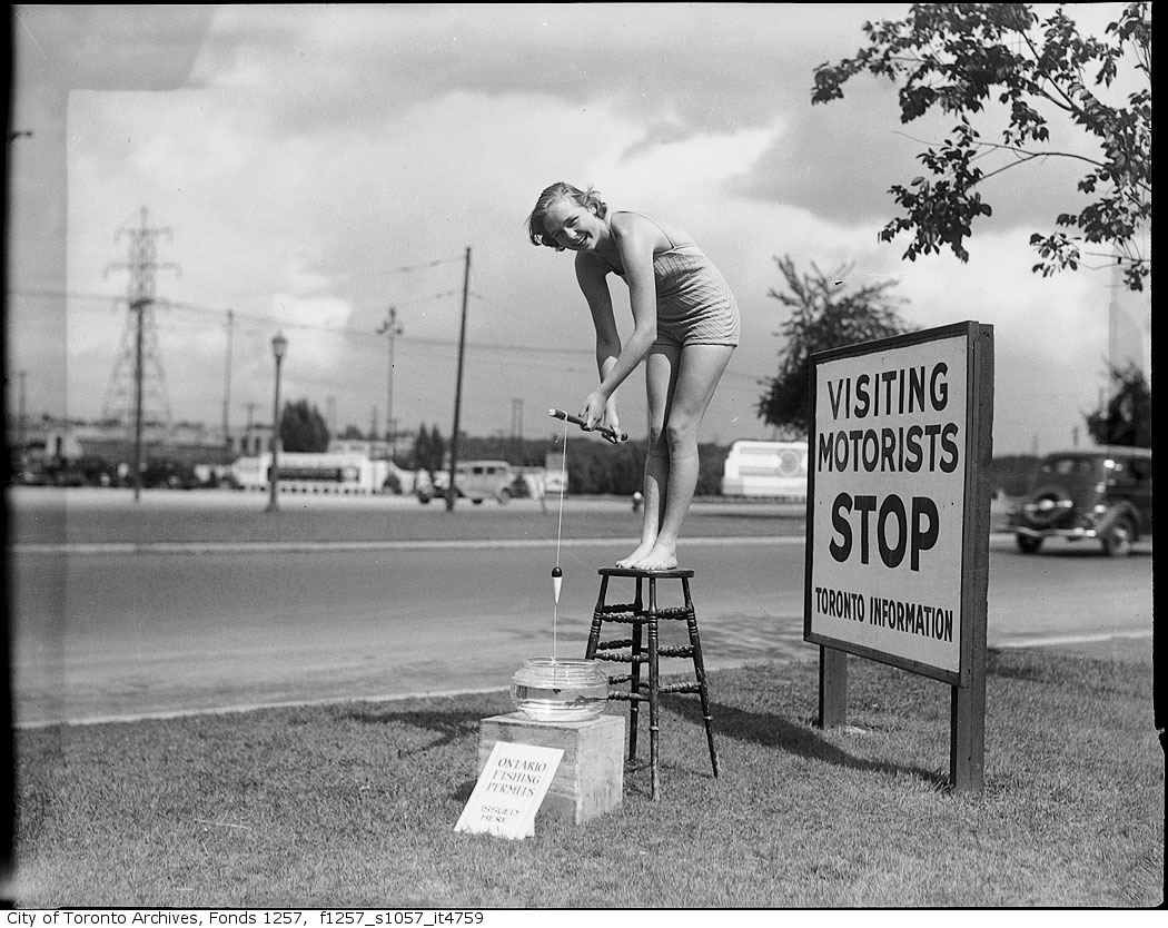193? - Woman fishing in gold fish bowl outside Toronto information booth - Vintage Fishing Photographs