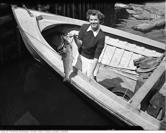 194? - Woman in boat, holding fish - vintage boating photographs