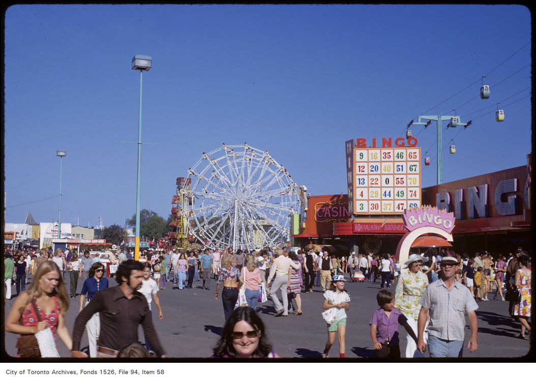 1972 - View of crowds on CNE grounds, ferris wheel and bingo and casino buildings in the background