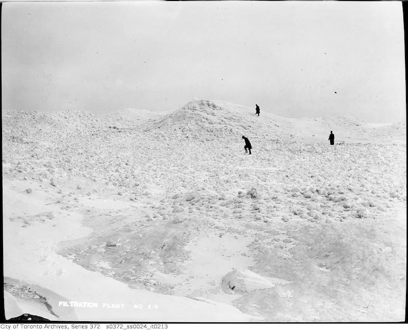 1911 - Island lake shore in winter showing snow and ice buildup, figures in distance