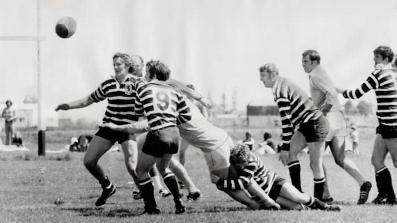 1974 - Touring English rugby team from Somerset (striped shirts) have situation well in hand as ball squirts loose during exhibition game against Ontario side at Fletcher Field