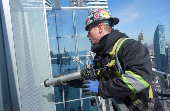 Chris caulking windows in a high rise office tower