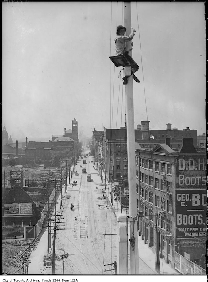 1907 - Flagpole painter with view looking west on Front Street from Yonge Street