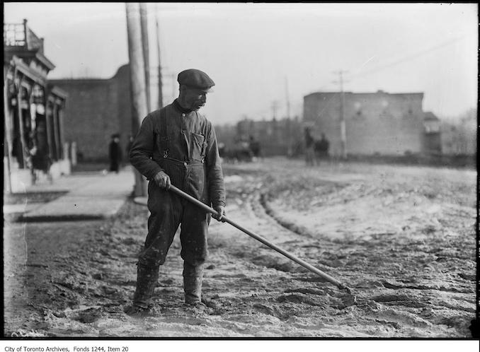 1911 - Man hoeing muddy road smooth, Yonge Street at Davisville Avenue