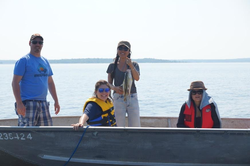 Fishing shot- Lora Kikuchi, in yellow life vest, looks on as one of the Teach for Canada teachers catches a fish during the community visit at Big Grassy River First Nation in late July.
