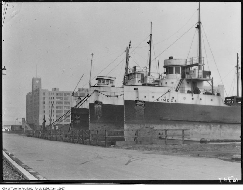 1929 - Waterfront, line of boats and warehouse in background