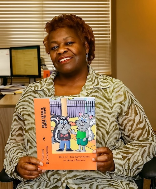 Yvonne Blackwood - Posing with my first children's picture book, Nosey Charlie Comes To Town