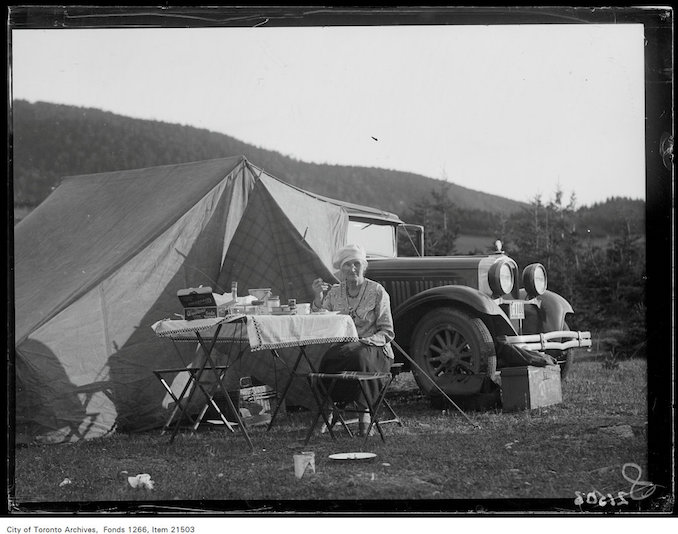 1930 - aug 8th - Holiday trip, Grande-Vallee, Mrs. John Boyd at table, car and tent background