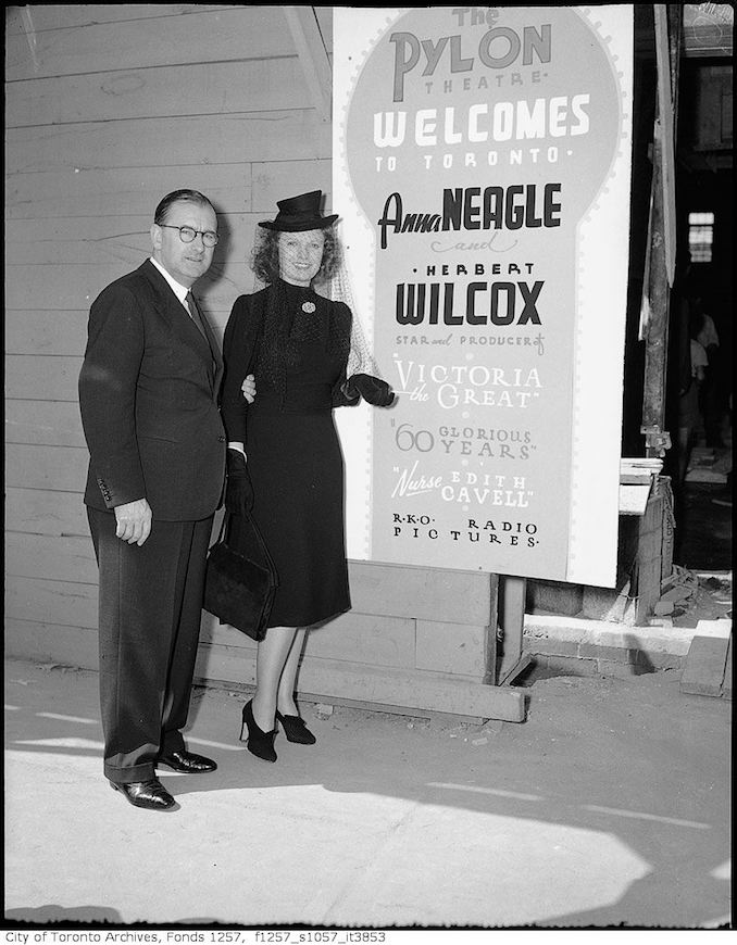 1939 - Anna Neagle and Herbert Wilcox, by sign advertising their movies