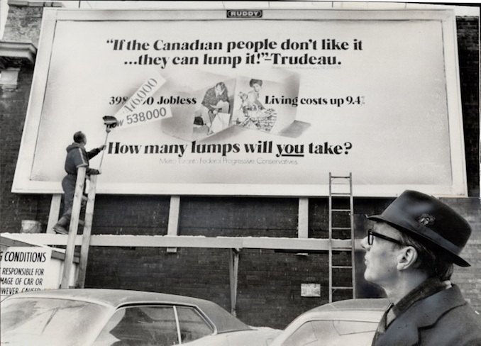1971 - Rising unemployment figures are posted on a Toronto billboard by workman Chris Hansen while Opposition leader Robert Stanfield - on nationwide tour to publicize unemployment problem