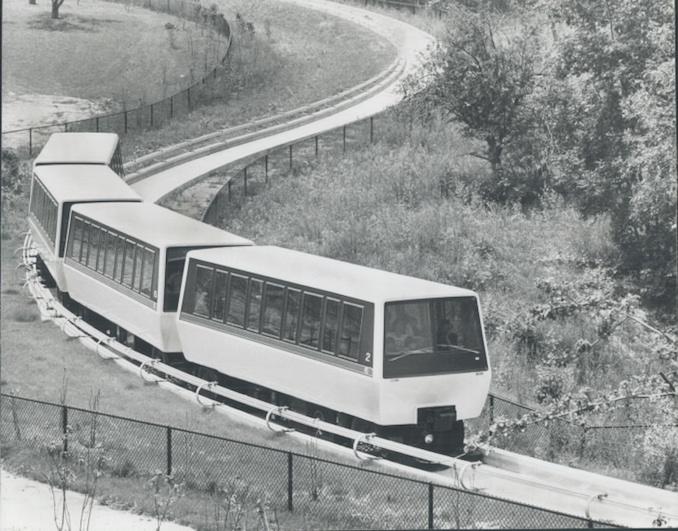 1976 - The electrically powered train travels along a concrete guideway winding through part of 410-acre Rouge River valley.