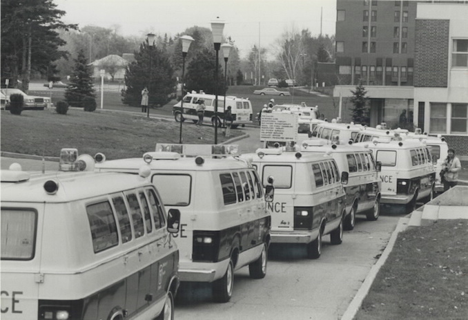 1979 - Jeff Goode - Some of the more than 85 ambulances; from as far away as Kingston; wait in line yesterday to move out patients from Mississauga General Hospital.
