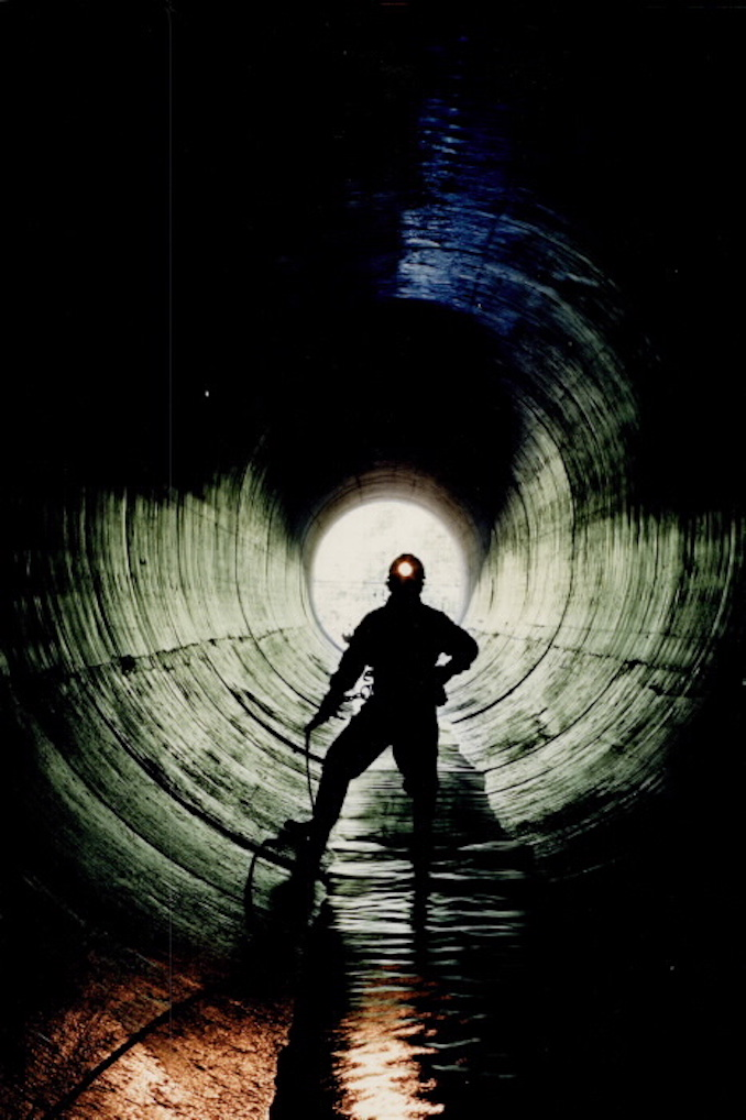 1987 - Bonie Bertumen stands in a 12-foot sewer; one of the many running below Metro. The smelll stops bothering you; he says; after working there 20 or 30 years - Mike Slaughter