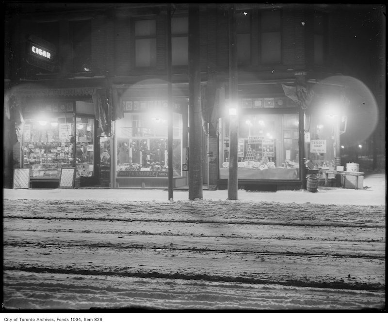 1922 - Exterior view of store fronts at 1498 Queen Street West, Parkdale, with Humphrey gas arc lighting, Sutherland tobacco, A. Grapple shoes, F. G. Martin, grocer