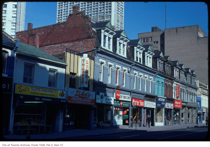 1975 - April 22 - View of stores along the west side of Yonge Street, south of Bloor Street West