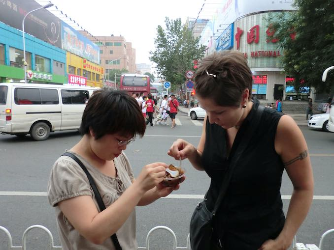 Jane Tingley - in Beijing, China for the exhibition of Plant(iPod)Installation in the Triennial for New Media Art 2011 – Tasting street food with my installation assistant