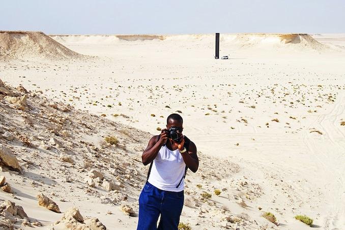 Ajani Charles photographing in Qatar's Zekreet Desert