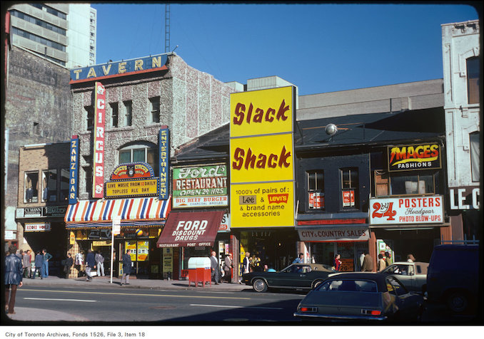 1975 - View of storefronts along Yonge Street on the east side, opposite Elm Street