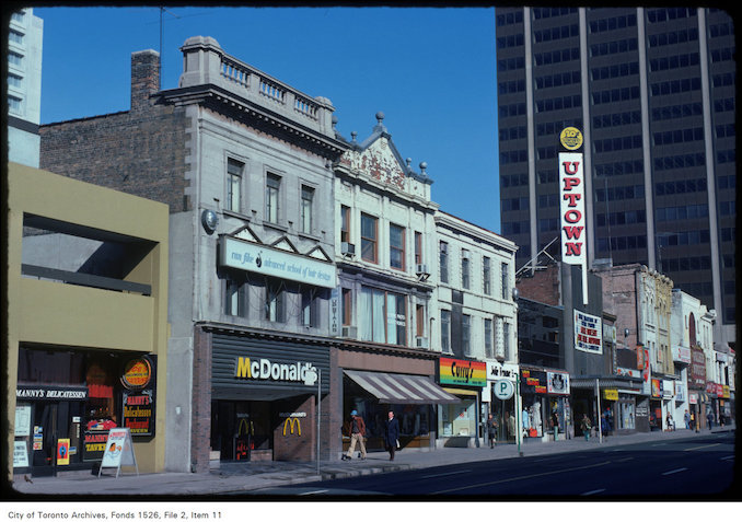 1975 - View of stores along the west side of Yonge Street, south of Bloor Street West