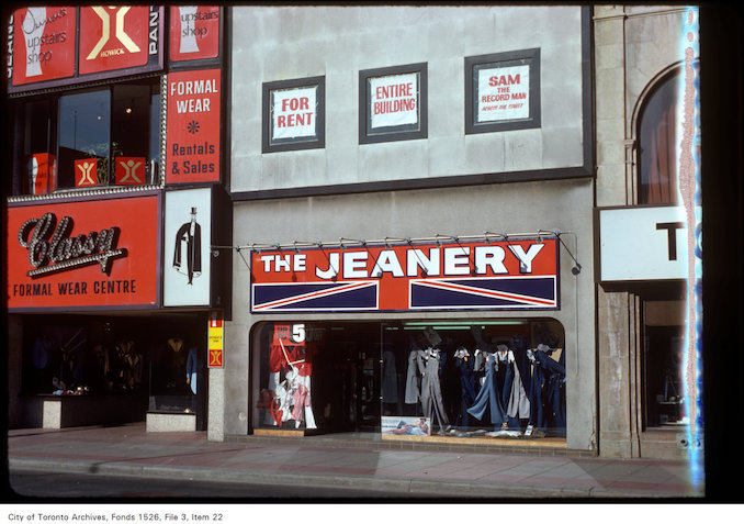 "1977 - View of ""the Jeanery"" and ""Classy"" formal wear centre on Yonge Street, south of Walton Street"